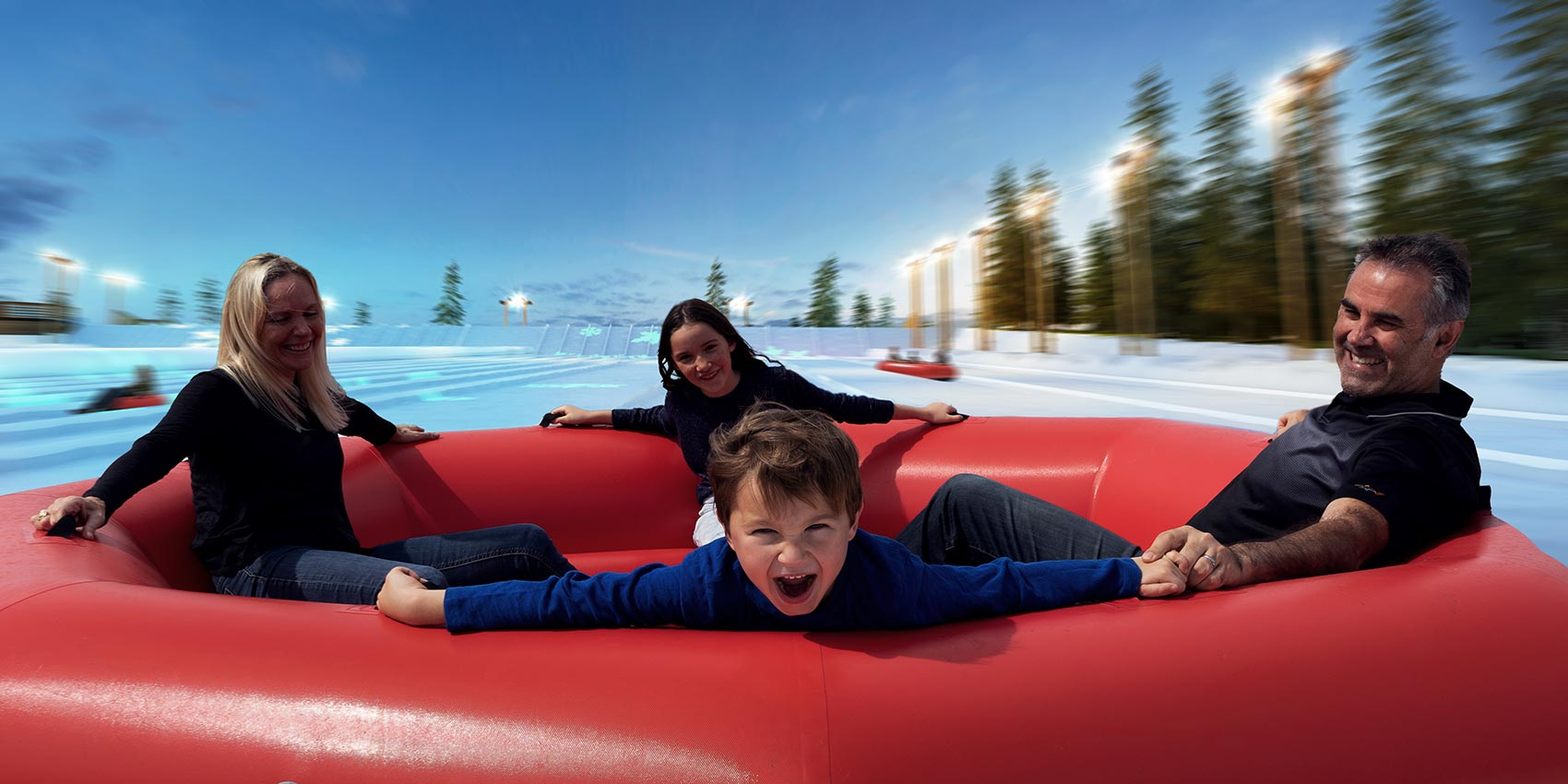 Family In Big Tube On Snowy Slopes